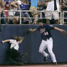 Twins third baseman Brian Buscher tries to cheer up this falling security guard by telling her she's safe.