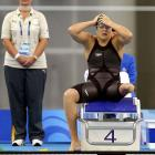 South Africa's Natalie du Toit adjusts her cap before the 100 butterfly.