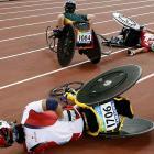 Japan's Wakako Tsuchiko, foreground, and Edith Hunkeleh of Switzerland lie on the track while Christie Dawes of Australia wheels away in the 5,000.