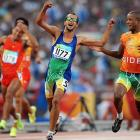 Lucas Prado of Brazil celebrates next to his guide (right) after winning the 100.