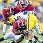 John Parker Wilson scored on a 1-yard sneak in overtime to clinch Alabama's spot in the Southeastern Conference championship game. Chales Scott (32) ran for 92 tough yards and two TDs for LSU.