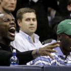 Terrell Owens, seated next to teammate Roy Williams, lets out a big cheer during Thursday's Suns-Mavericks game in Dallas.