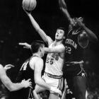UCLA guard Gail Goodrich (25) attempts to get a shot past Michigan's Cazzie Russell during the Final Four held in Portland. UCLA won 91-80 to take the title.