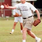 Jimmy Carter tosses a pitch during a softball game between the alumni of Plains High and Carter's Secret Service team. The softball game was part of the closing of the Peanut Festival in Plains, Ga.