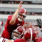 Alabama quarterback Greg McElroy celebrates with  offensive lineman Mike Johnson and tight end Baron Huber after a touchdown pass to Julio Jones in the SEC opener for Alabama. McElroy passed for a career-high 291 yards and three touchdowns.