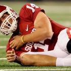 Heisman Trophy winner Sam Bradford sprained his throwing shoulder after being slammed to the turf in the first half. He completed 10 of 14 passes for 97 yards and a touchdown.