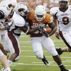Texas' Cody Johnson, center, powers his way toward the end zone. The 5-foot-11, 255-pound freshman carried 11 times, second on the team, and scored three times for the Longhorns.