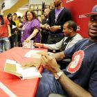 """The ultimate collector's edition: Adoring fans wait patiently as LeBron James writes the first 500,000 copies of his new book, """"Shooting Stars,"""" entirely by hand."""