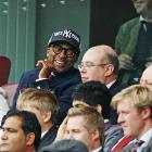 The famed director and budding phrenologist gazes into the future and obviously likes what he sees for his beloved New York Knicks as he studies the shape of a patron's skull at a recent Premier League soccer match in London.