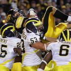 Iowa's Brandon Wegher leaps over Michigan defenders Kenny Demens, Ryan Van Bergen (53) and Donovan Warren (6) while scoring a touchdown during the second quarter. The Hawkeyes are 6-0 and have won 10 consecutive games, dating to last season.