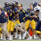 West Virginia's Noel Devine (center) races past head coach Bill Stewart (left) and by Connecticut's Jerome Junior to complete a 56-yard touchdown run with 2:10 left in the game. Devine rushed for 171 of his game-high 178 yards in the second half as the Mountaineers rallied to improve to 6-1.
