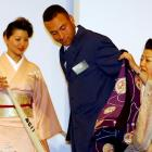"""Japanese women clad in a traditional kimono dress assists Jeter as he puts on a """"happi"""" coat during a welcome reception for the Yankees and Devil Rays at a Tokyo hotel in March 2004."""