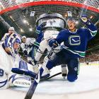 Joey MacDonald of Toronto sits dejected in the crease as Mason Raymond of Vancouver celebrates a goal. Raymond had two goals as the Canucks defeated the Maple Leafs 3-1.