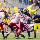 "Michigan's Jon Conover hurdles an Indiana lineman and nearly blocks a punt by Chris Hagerup during the teams' Big Ten opener in Ann Arbor on Sept. 26. The Wolverines prevailed 36-33 to get off to a 4-0 start.<br><br>""I was running from end zone to end zone following the football but decided to stop for a shot of this punt, since both teams had come close to blocking a number of kicks. At first glance I didn't think much of the shot, since the punt wasn't blocked. Then I took a second look."" -- Photographer Eric Bronson/ICON SMI"