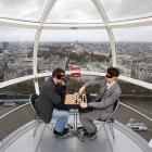 English grand master Nigel Short (left) and Luke McShane engage in a friendly game of blindfold chess in a capsule atop the London Eye on Dec. 7. Reports indicate the match is still going as several pieces were knocked to the floor and the players are groping for them.