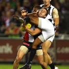 Leon Davis of the Collingwood Magpies tackles Adam Schneider of the St Kilda Saints during their Australian rules football match on April 9 in Melbourne.
