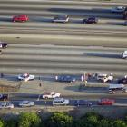 Motorists exit their vehicles to watch the action as police follow the white Bronco from a safe distance.