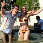 For those who  insist  that swimwear on a comely lass has a tenuous, at best, connection to sports, we counter with this soccer partisan and her friend celebrating in a fountain in Munich after Germany's World Cup win over Argentina.