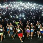 """Thousands of runners use headlights to participate in the """"Energizer night race"""" July 10 in Mandaue, Cebu City, Central Philippines. The event was held as part of a run-for-a-cause for the benefit of hearing-impaired children in the province of Cebu."""