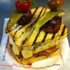 A grilled triple stack of Pullman bread, loaded with smoked brisket, pulled pork, coleslaw, bbq meatball, pickle and cherry peppers.