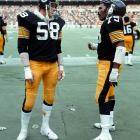"""Steelers linebacker Jack Lambert and defensive tackle """"Mean"""" Joe Greene chat before a home game against the Broncos. Lambert had an interception in the game."""