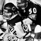 Gary Fencik and Mike Singletary, part of the ferocious 1985 Chicago Bears defense, plows over Eddie Lee Ivory of the Green Bay Packers in a 23-7 Bears win.