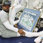 Smith checks out a poster featuring fellow Phi Beta Sigma brothers (and Cowboy teammates) James Washington (37) and Erik Williams (79).