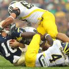 Notre Dame quarterback Nate Montana takes a foot in the face from safety Cameron Gordon as Mike Martin assists on the tackle during Michigan's 28-24 win in South Bend, Ind., on Sept. 11.