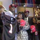 Vick holds up an Atlanta Falcons jersey after being selected as the No. 1 overall pick in the NFL draft. Vick is surrounded by members of his family, including his mother, Brenda Boddie.