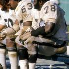 Future Hall of Fame linemen Gene Upshaw and Art Shell take a breather on the Raiders bench.