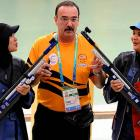 Bronze medalist Mohamed Taibi Nur Suryani (left) and silver medalist Halim Nur Ayuni of Malaysia demonstrate one surefire way to make an official show a little favoritism in the 10m air rifle event.
