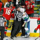 The Vancouver Canuck forward (center) found himself in the loving embrace of linesman Don Henderson after coming off the spool during a game against the Minnesota Wild on Oct. 19. Alas, Rypien continued going wild and aroused the ire of the NHL by grabbing and shaking a heckler on the way to the dressing room.