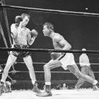 Pender ( left ) outpointed an aging Sugar Ray Robinson for the lineal title in January 1960, retaining it against Robinson in the rematch before defenses against Terry Downes and Carmen Basilio. He'd lose it to Downes in the middle installment of their trilogy.