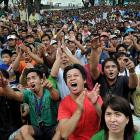 Filipinos celebrate as they watch a live satellite broadcast of the fight at a free public viewing Sunday in Marikina, east of Manila.