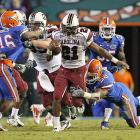 After years of being the top Gator, Steve Spurrier led South Carolina to its first division crown in the stadium he nicknamed The Swamp. Marcus Lattimore (No. 21) ran 40 times for a career-high 212 yards and three TDs, Stephen Garcia played turnover-free South Carolina clinched the Southeastern Conference's Eastern Division. The Gamecocks won for the second time in 19 tries against Florida, snapped an 0-for-12 streak in Gainesville and earned a spot in the league title game for the first time. South Carolina (7-3, 5-3 SEC) will play second-ranked Auburn on Dec. 4, with the winner advancing to the Bowl Championship Series.