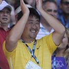 Jiang Shan, coach and husband of Li Na, applauds his wife as she speaks to the crowd following her win over Wozniacki.