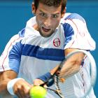 Novak Djokovic of Serbia hits a backhand return to compatriot Viktor Troicki during their third-round match Friday at Melbourne Park. Troicki retired with stomach problems after Djokovic won the first set.