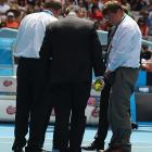 Officials assess the court surface at Hisense Arena after reports that the ball was not bouncing properly.