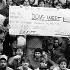 A fan holds up a sign mocking a bribery allegation before a Pittsburgh-Villanova game on Feb. 7, 1986. Doug West, a highly-touted Villanova freshman, had alleged to a Louisville newspaper that a Pittsburgh booster had offered him money to play basketball for the Panthers.