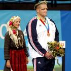 Gardner stands with an Olympic representative during the 2004 medal ceremony.  Gardner won bronze in 2004, and shortly thereafter retired from competitive wrestling.