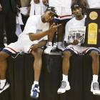 Hilton Armstrong (left) and Ben Gordon celebrate with the trophy and newspaper headline after the Huskies won the national championship with an 82-73 win over Georgia Tech.
