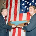 """Dennis Conner, captain of America's Cup champion """"Stars and Stripes,"""" receives a model of his winning yacht from Trump during a reception in February 1987. Trump was one of Conner's financial backers; he even paid for a victory parade in New York."""