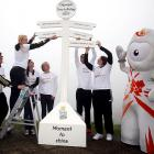 """Human youngsters got help from an illegal alien constructing the 2012 Olympic Torch relay sign at Lands End in Cornwall, England. If you can't quite make out what's on each arrow, we assume it's helpful directions like """"Turn left at Neptune."""""""