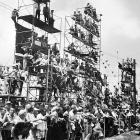 The crowd watches what some consider to be the best Indy 500 ever. Eventual winner Jim Rathmann and defending champion Rodger Ward swapped the lead 14 times during the second half of the race, but Ward was ultimately forced to slow with three laps remaining because of a worn tire.