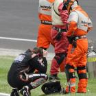 JR Hildebrand reacts next to track safety personnel after he crashed on the final lap.