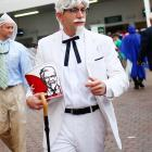 A man dressed as Colonel Sanders makes his way through Churchill Downs, bucket in hand.