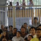Filipinos cling onto the gates to watch Pacquiao fight during a live television broadcast inside the Makati city jail south of Manila. Much of Pacquiao's poor Southeast Asian nation grounded to a halt as Filipinos stayed glued on screens from pricey hotel bars to a crowded jail and public plazas.