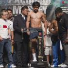 Pacquiao stands on the scale flanked by his trainer Freddie Roach (far left) and Mosley's trainer Naazim Richardson (right).