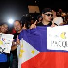 Francis Ramos, Alex Cagalawan and Bing Oamilda, fans of Manny Pacquiao, hold signs before the weigh-in.
