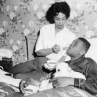 Mays' wife, Marguerite, feeds him soup while his dog Pope licks his hand during spring training in 1957. Mays missed a day of practice with a virus. Mays and Marguerite married in 1956 but divorced approximately six years later.